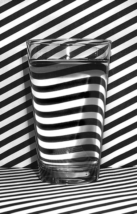 glass-of-water-on-black-and-white-striped-background