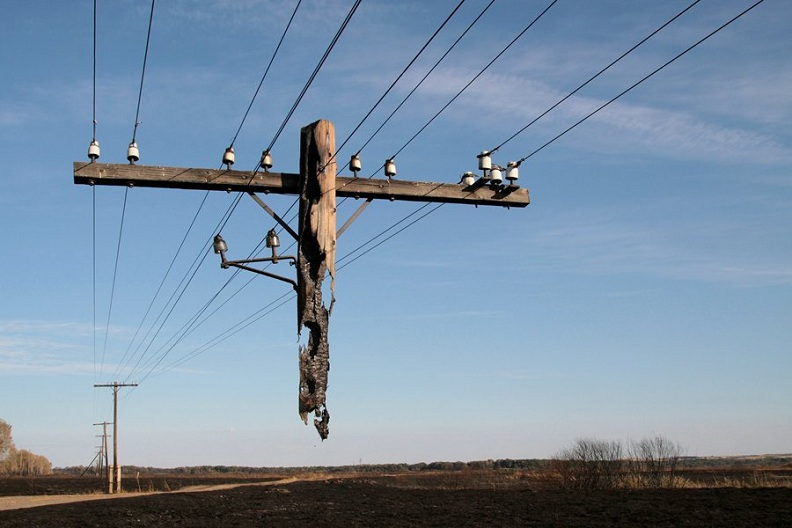 half burnt telephone pole hanging off wires Picture of the Day   Broken Telephone