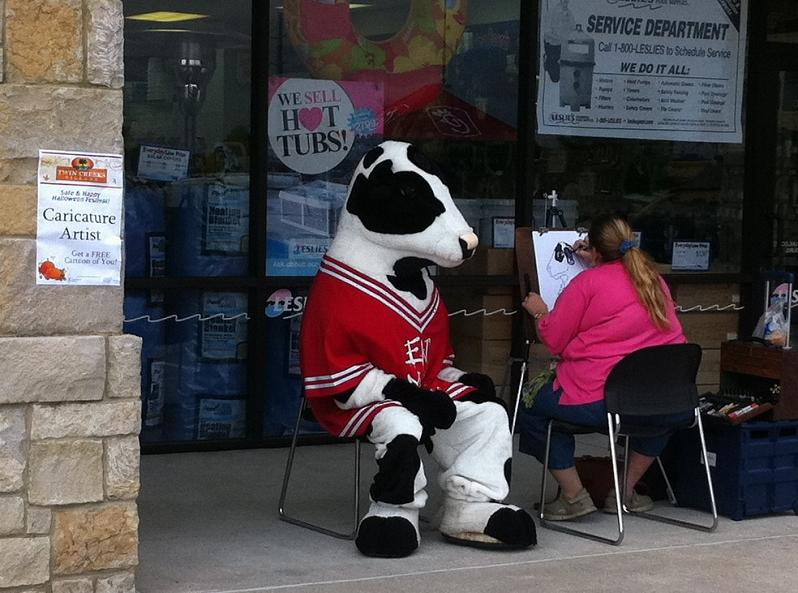 man-in-cow-costume-getting-drawn-on-sidewalk