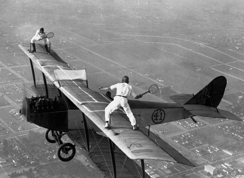 Fotografía antiguas, históricas y poco conocidas Playing-tennis-on-wings-of-plane-vintage-daredevils-black-and-white