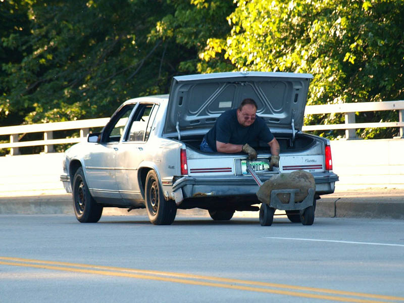 man sitting in trunk of car using dolly to move big The Friday Shirk Report   Volume 117