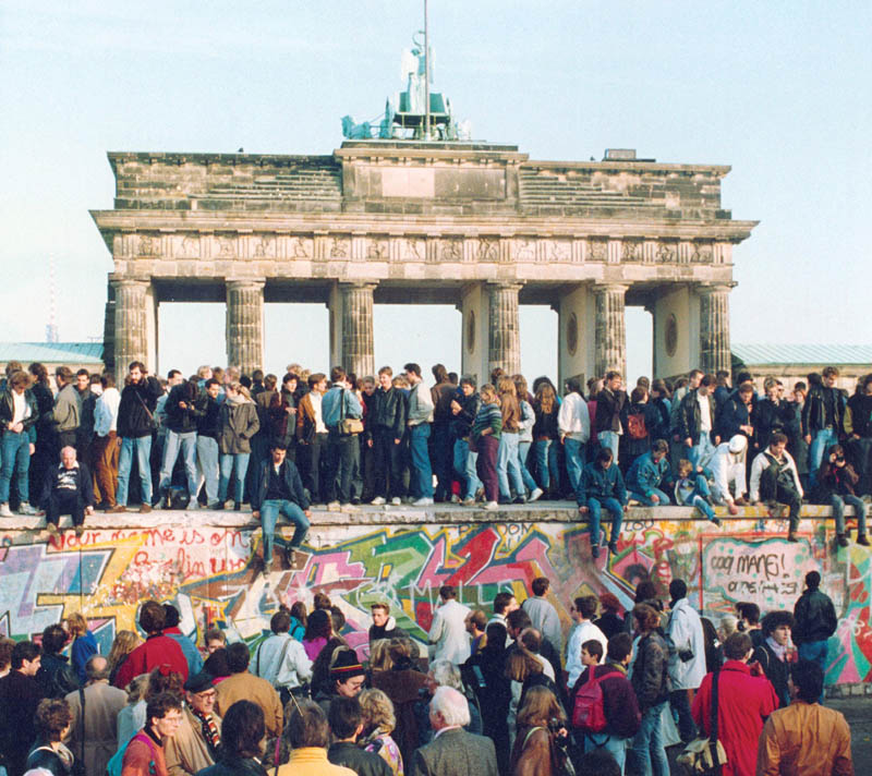 fall of berlin wall 1989 people standing dancing on wall This Day In History   November 9th