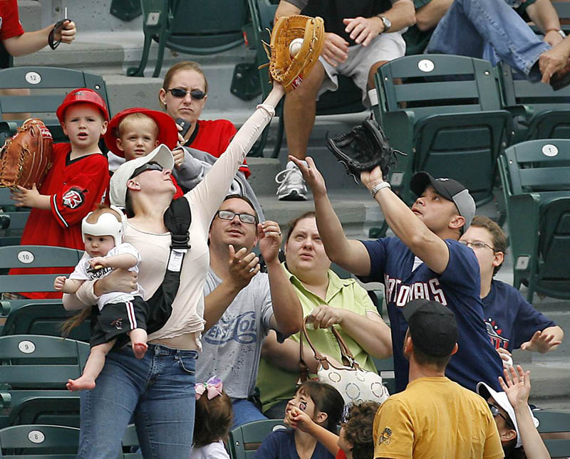 super mom catching baseball holding baby Picture of the Day: Super Mom!