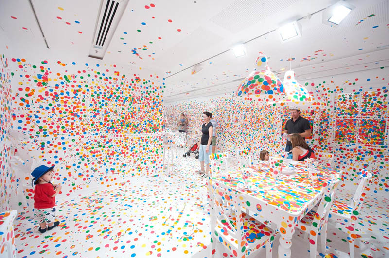 white room covered in stickers by kids yayoi kusama obliteration room 10 Kids Turn White Room into Explosion of Color
