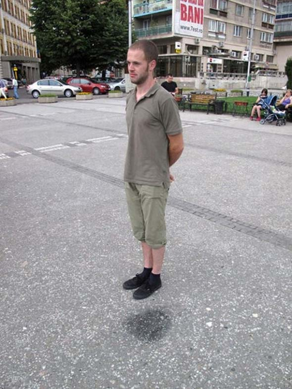 standing beside dark spot on ground hovering 12 Optical Illusions Made from Shadows
