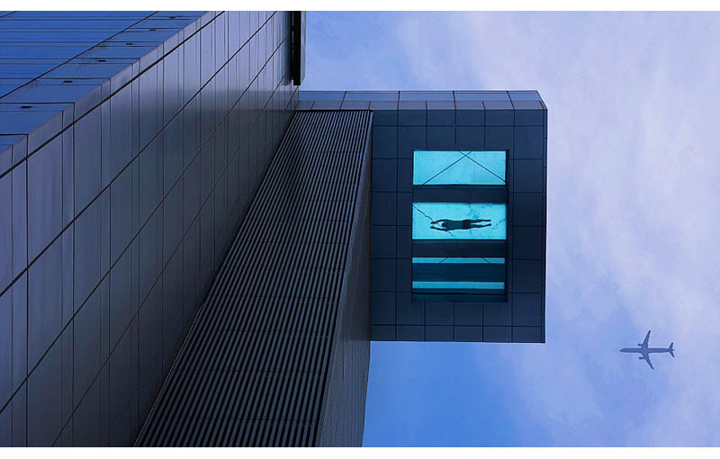 view from below looking up at the 24th floor glass bottomed pool that overhangs the street at the holiday inn in shanghai china