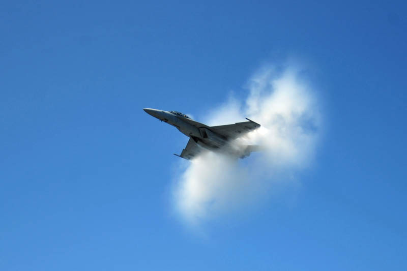 plane emerges from small looking cloud as result of breaking speed of sound