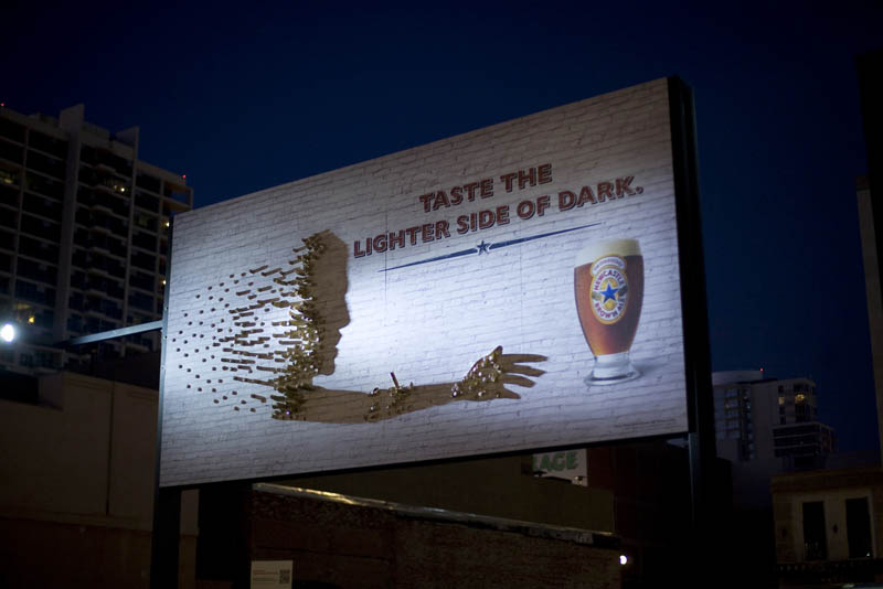 beer billboard using light to create shadow of person reaching for a beer