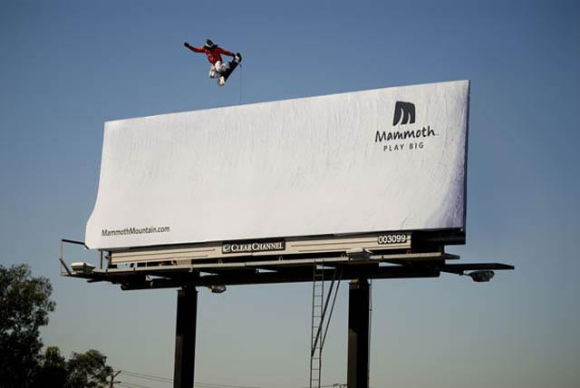 snowborder doing big air grab off billboard