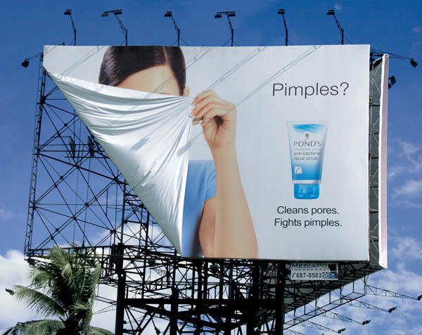 ponds billboard shows woman hiding face with part of billboard because of pimples