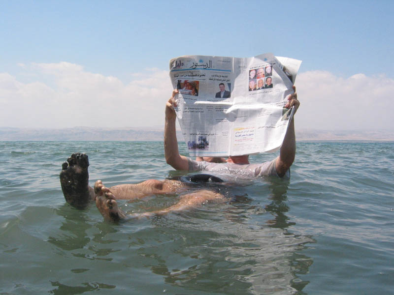 person floating in the dead sea reading a newspaper