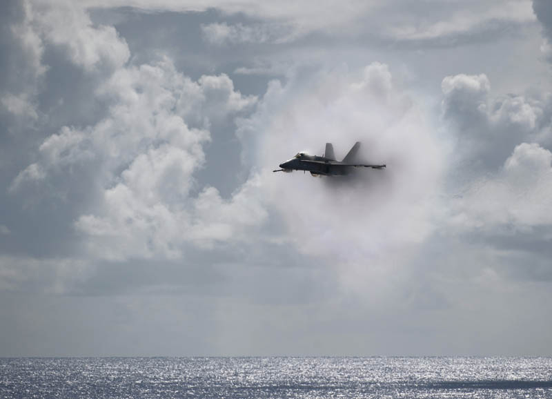 plane going supersonic mach 1 amongst clouds