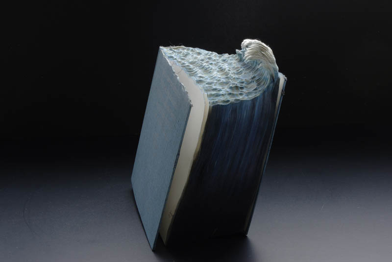ocean wave carved into top of pages of book