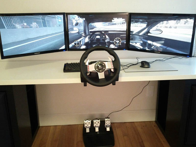 three monitor set up for racing game with steering wheel and pedals