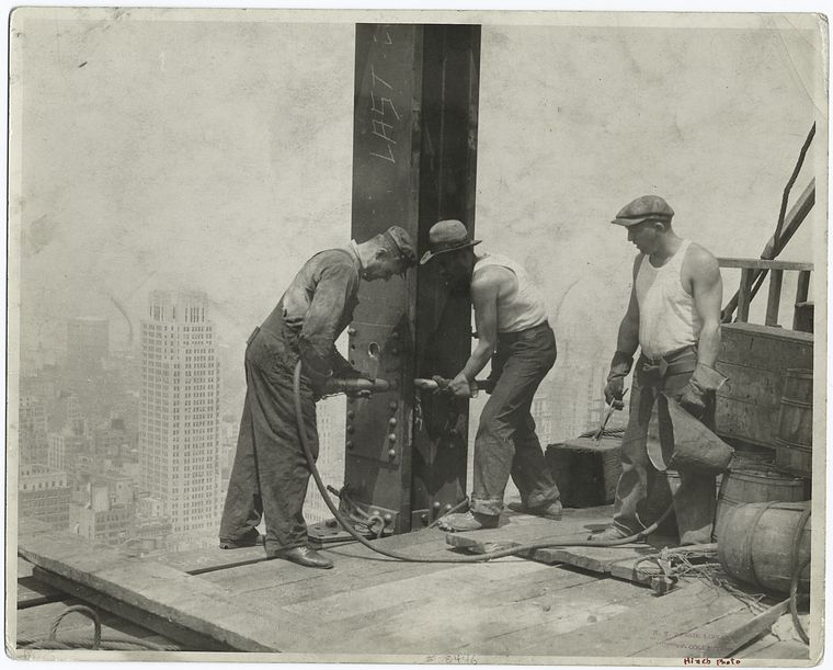 Three workers securing a rivet high up the empire state building