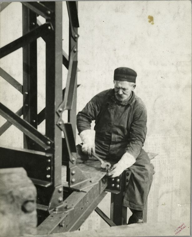 worker attaching bolt to beam no harness sitting on edge at top of empire state building 1931