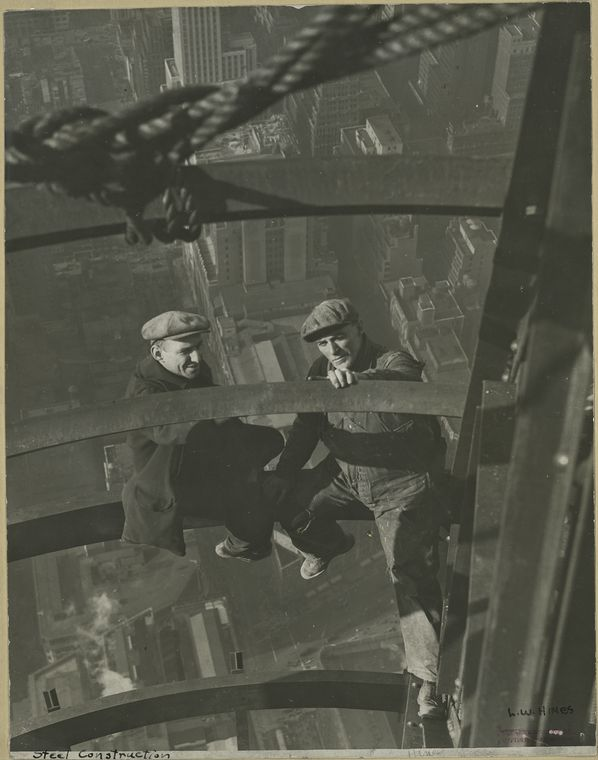 Two workers inspecting steel high up no harness city in backdrop