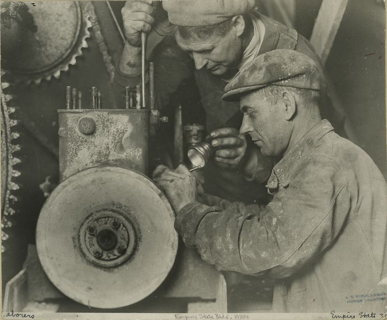 Two workers repairing machinery (1931)