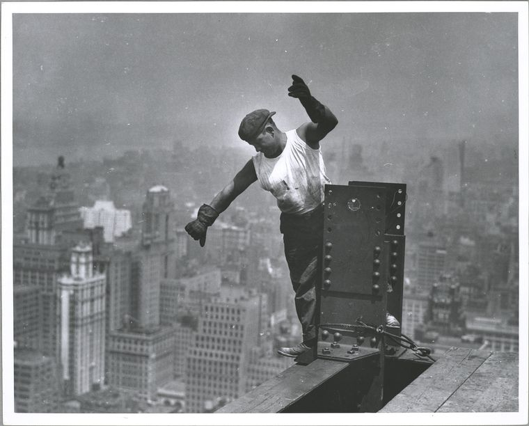 Worker on Empire State building, signaling the hookman high up unsecured standing on beam