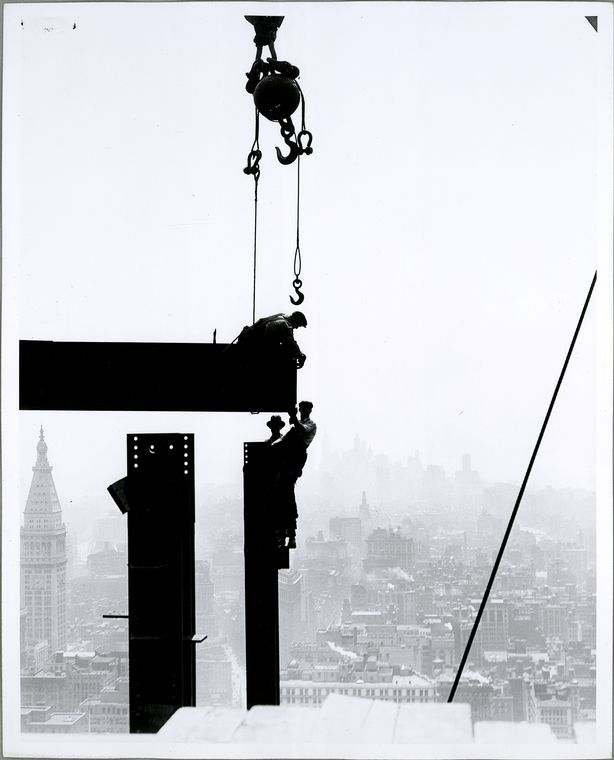 silhouette of Workers on Empire State building with city in background