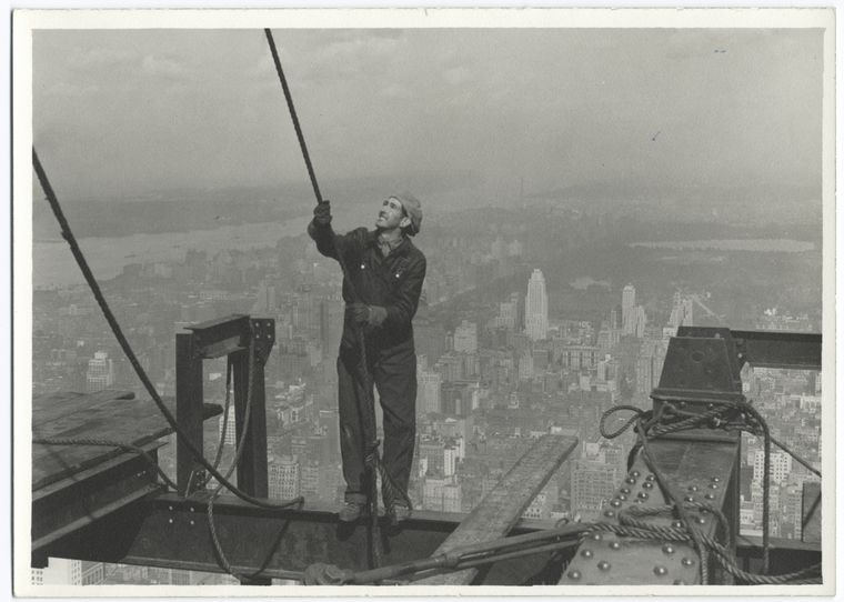 Construction worker standing on an I-beam pulling a rope (1931)