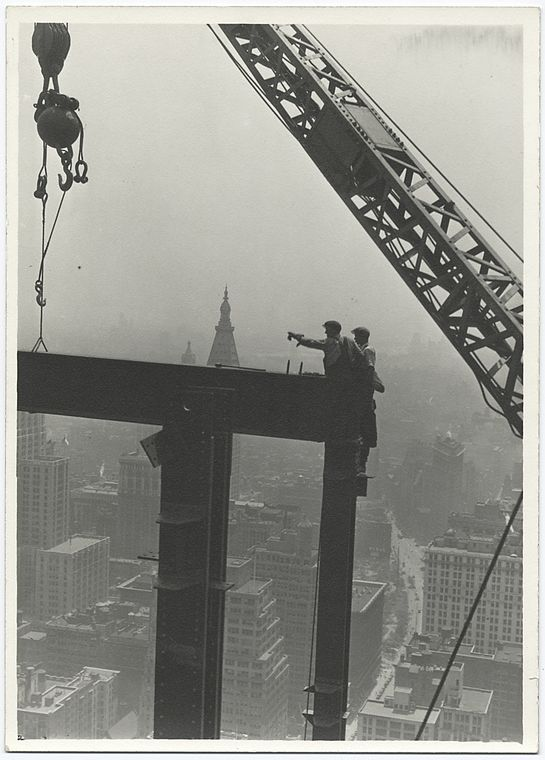 Two construction workers at the corner of two steel beams pointing to the left (1931)