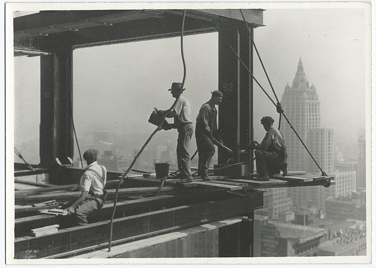 Riveters attaching a beam sitting on small wooden platform unsecured 1931