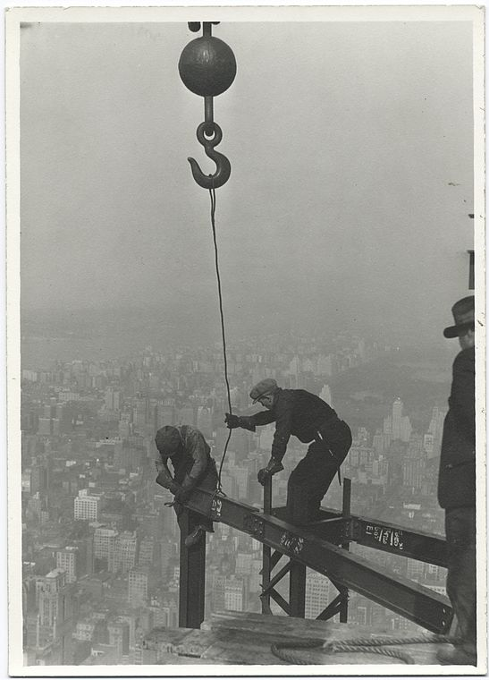 two workers attaching beam with a crane high up empire state building 1931 no safety harnesses