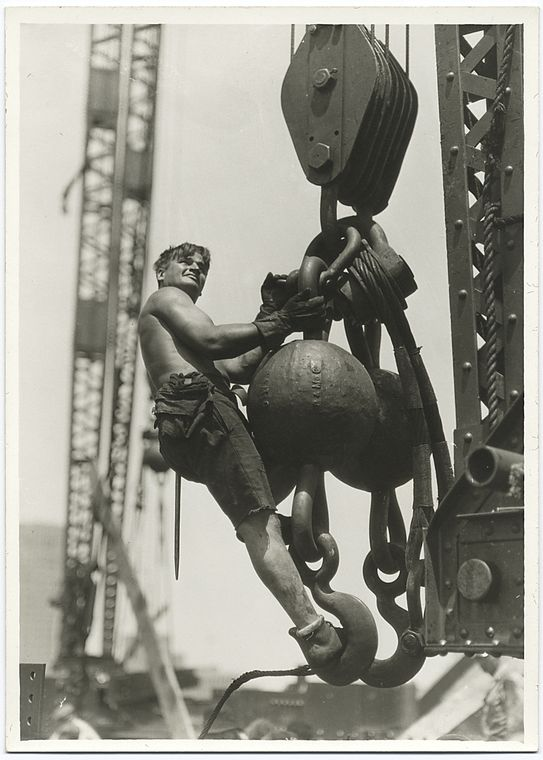 a worker riding on a massive crane hook