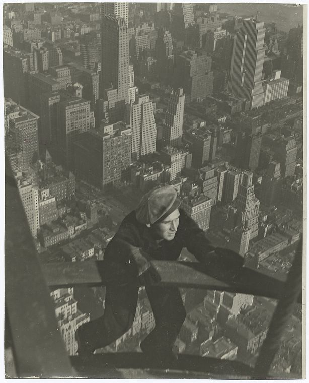 a worker hanging on two steel beams very high up with city of new york in background
