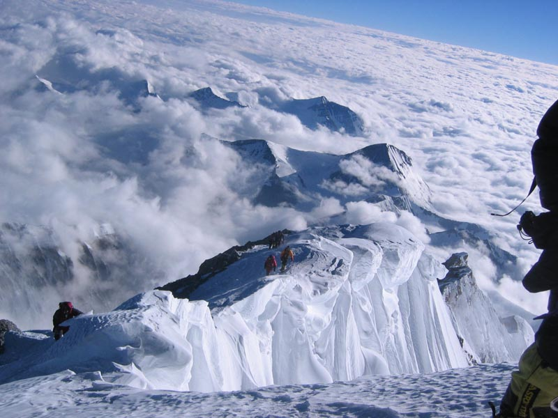 view from summit of other climbers approaching the summit