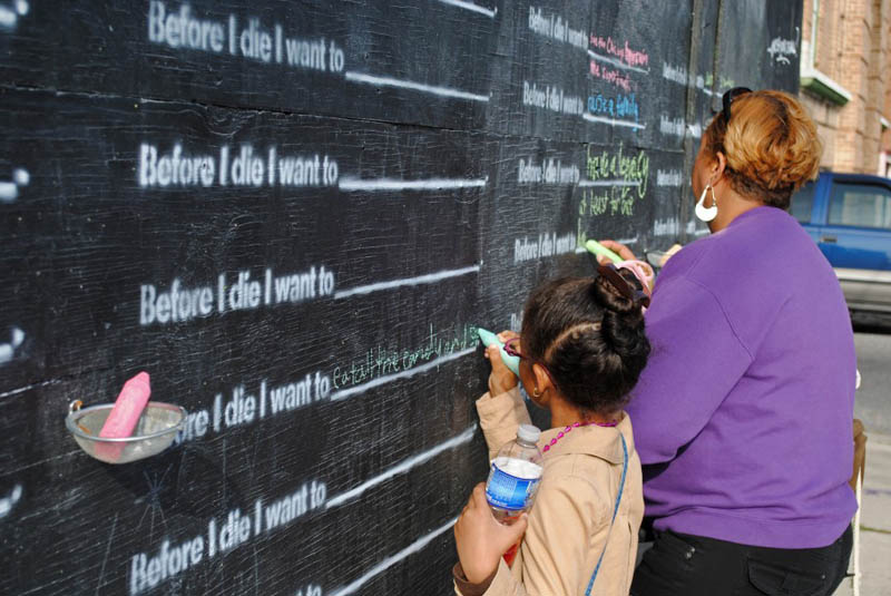 mother and daughter writing on the before i die wall in new orleans