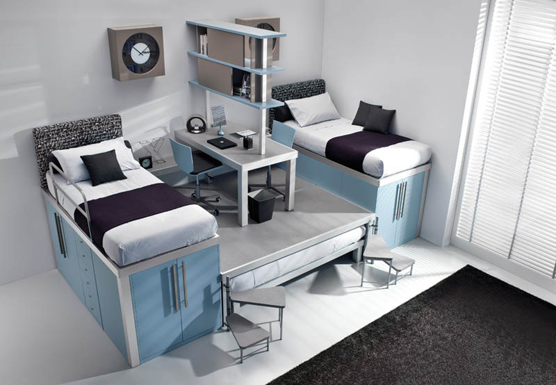 raised bunk beds with storage underneath and desk in the middle with a third bed underneath