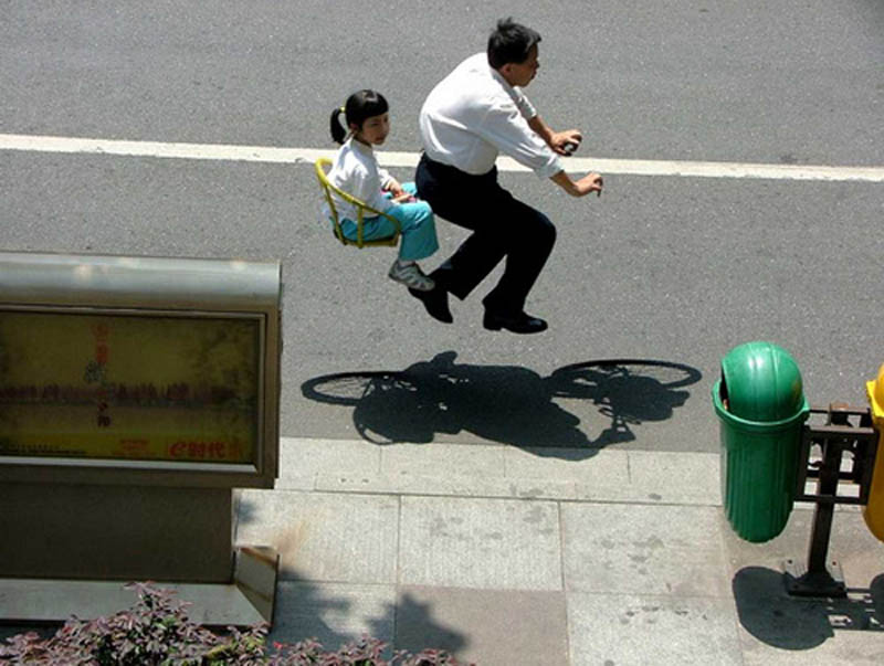 father and daughter riding invisible bike look like they are flying