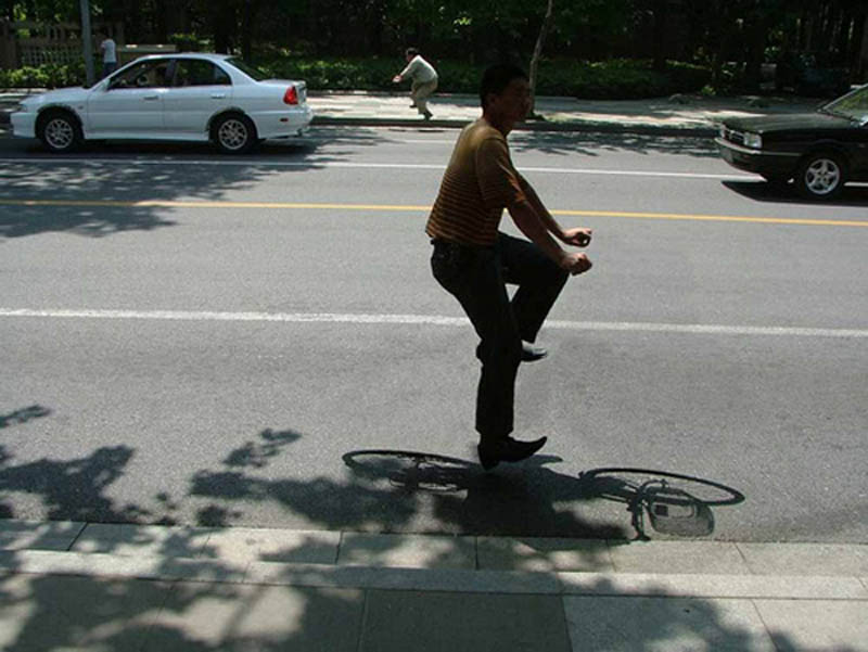 portrait of person riding an invisible bike with shadow of bike still visible
