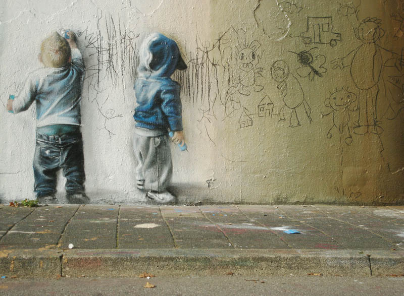 street art of two kids drawing scribbling on wall