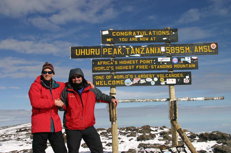 two climbers in front of sign at the top of mount kilimanjaro the highest point in africa