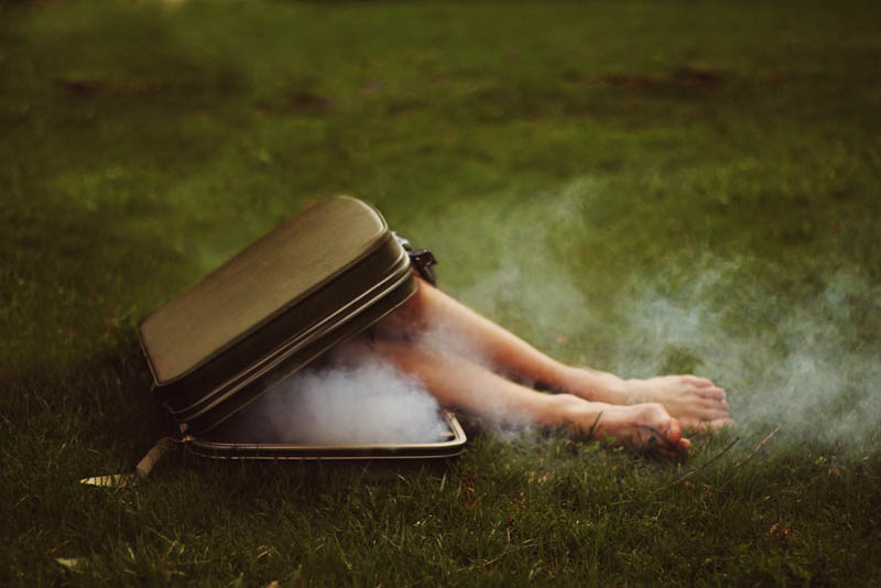 kyle thompsons feet coming out of a smoking briefcase surreal self portrait