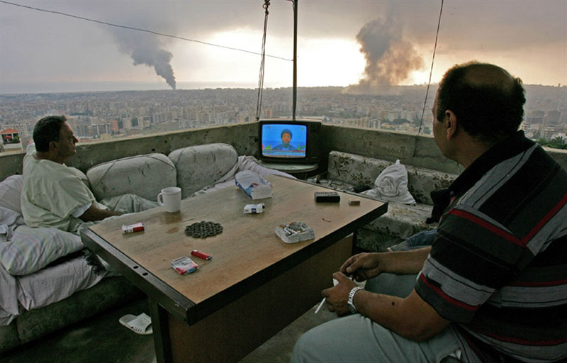 people watching tv on balcony with black smoke rising in background beirut lebanon Picture of the Day: Watching War Unfold