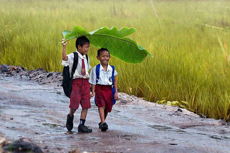 two kids under a banana leaf in the rain indonesia National Geographics 2013 Photo Contest Winners Gallery