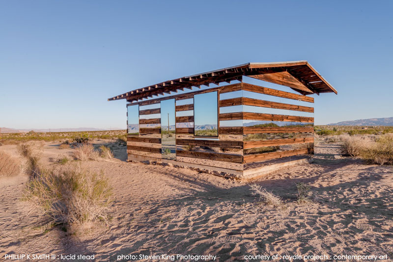 a transparent cabin of wood and mirrors on a desert