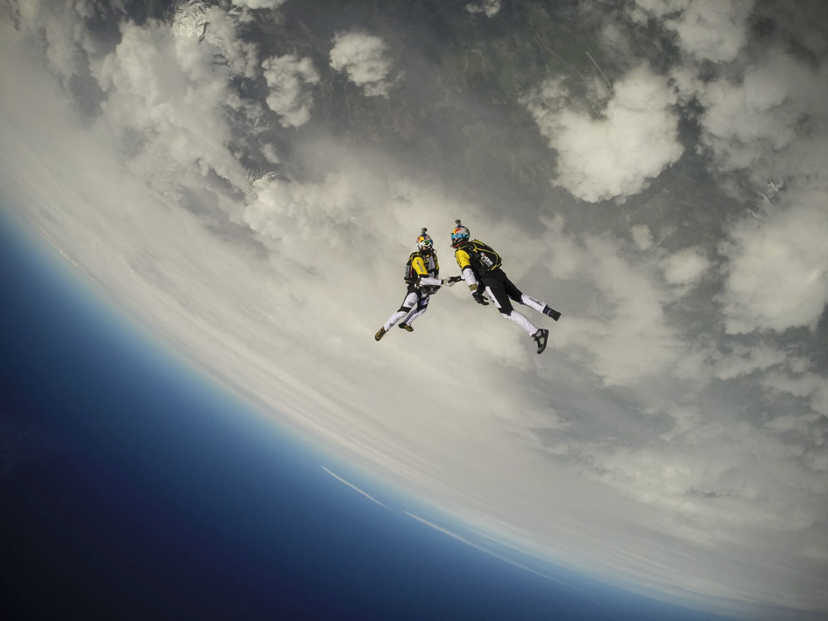 skydivers shaking hands mid-air