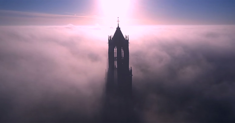 drone footage of the dom tower of utrecht on a foggy day