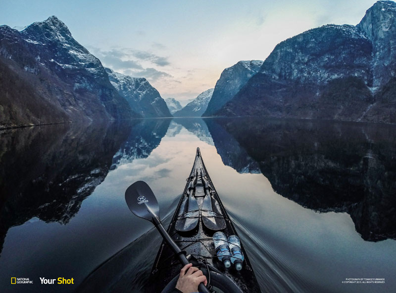 This photo was taken in wintertime after sunset in Norway. I was kayaking in the evening in the area where Aurlandsfjord meets Nærøyfjord. I waited until the water got completely calm at about 20 minutes after sunset. I saw through my gopro app on my phone that the gopro was using exposure of 1/30 sec due to the low light. I had to keep absolutely still while gliding slowly in the water to get a good photo without blur. The paddle back to the car took over an hour in darkness with a headlamp.