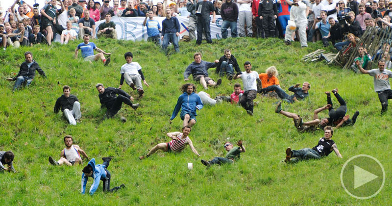 Slow Motion Wipeouts of People Chasing Cheese Down a Hill Set toClassical
