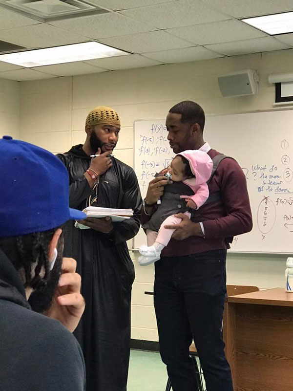 teacher holds students baby during lecture 1 Teacher Goes Viral After Holding Students Baby So They Could Take Notes