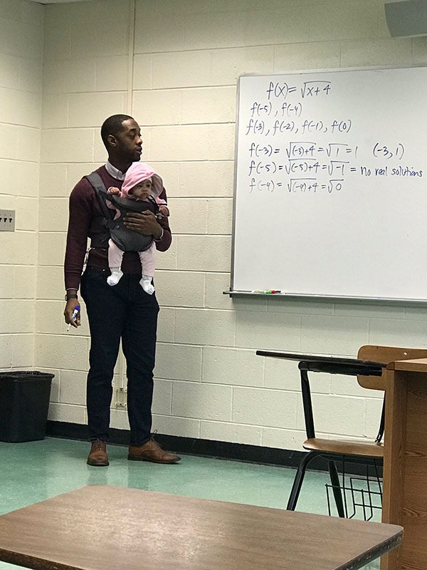 teacher holds students baby during lecture 4 Teacher Goes Viral After Holding Students Baby So They Could Take Notes
