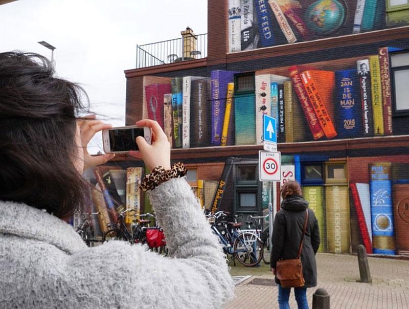 giant 3d bookshelf street art by jan is de man and deef feed 1 Dutch Artists Paint Giant 3D Bookshelf of Neighborhoods Favorite Books