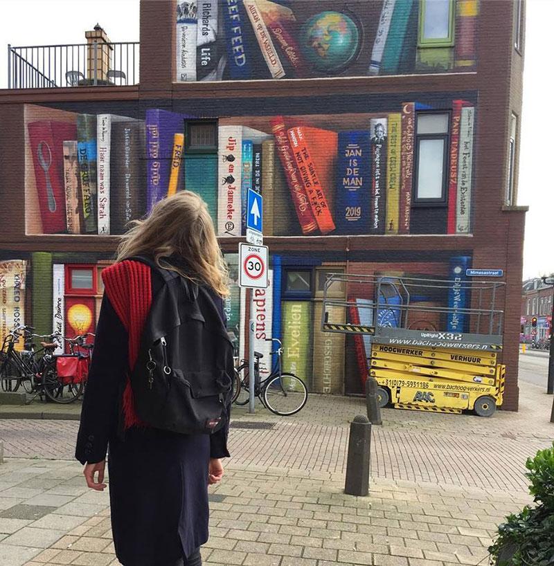 giant 3d bookshelf street art by jan is de man and deef feed 2 Dutch Artists Paint Giant 3D Bookshelf of Neighborhoods Favorite Books