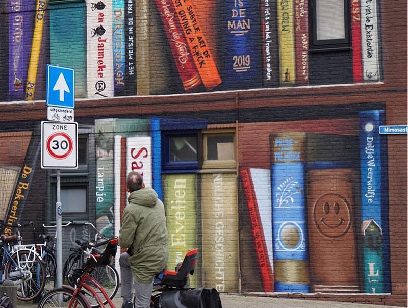 giant 3d bookshelf street art by jan is de man and deef feed 3 Dutch Artists Paint Giant 3D Bookshelf of Neighborhoods Favorite Books